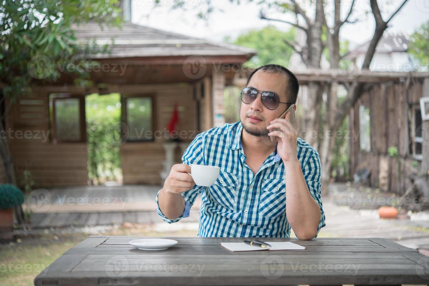 jeune homme d'affaires à l'aide de smartphone tout en travaillant dans le jardin potager photo
