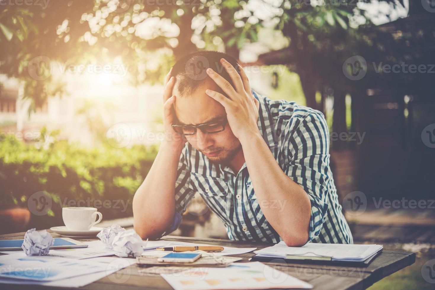 homme d'affaires stressé avec des papiers et des graphiques assis à table à la maison photo