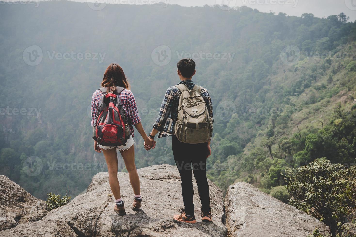 couple de randonneurs avec des sacs à dos debout au sommet d'une montagne et profiter de la vue sur la nature photo