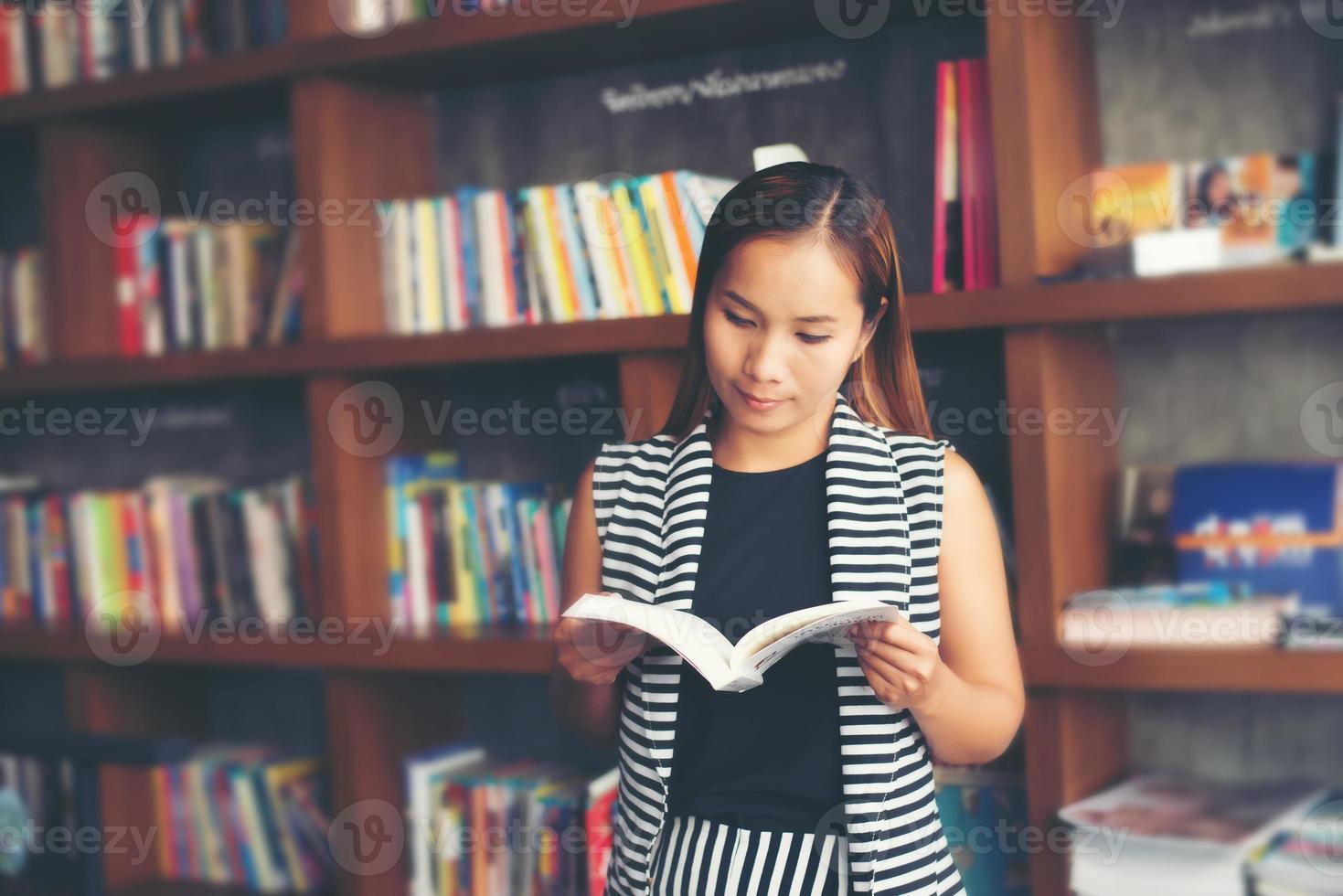 femme asiatique, lecture livre, dans, bibliothèque photo
