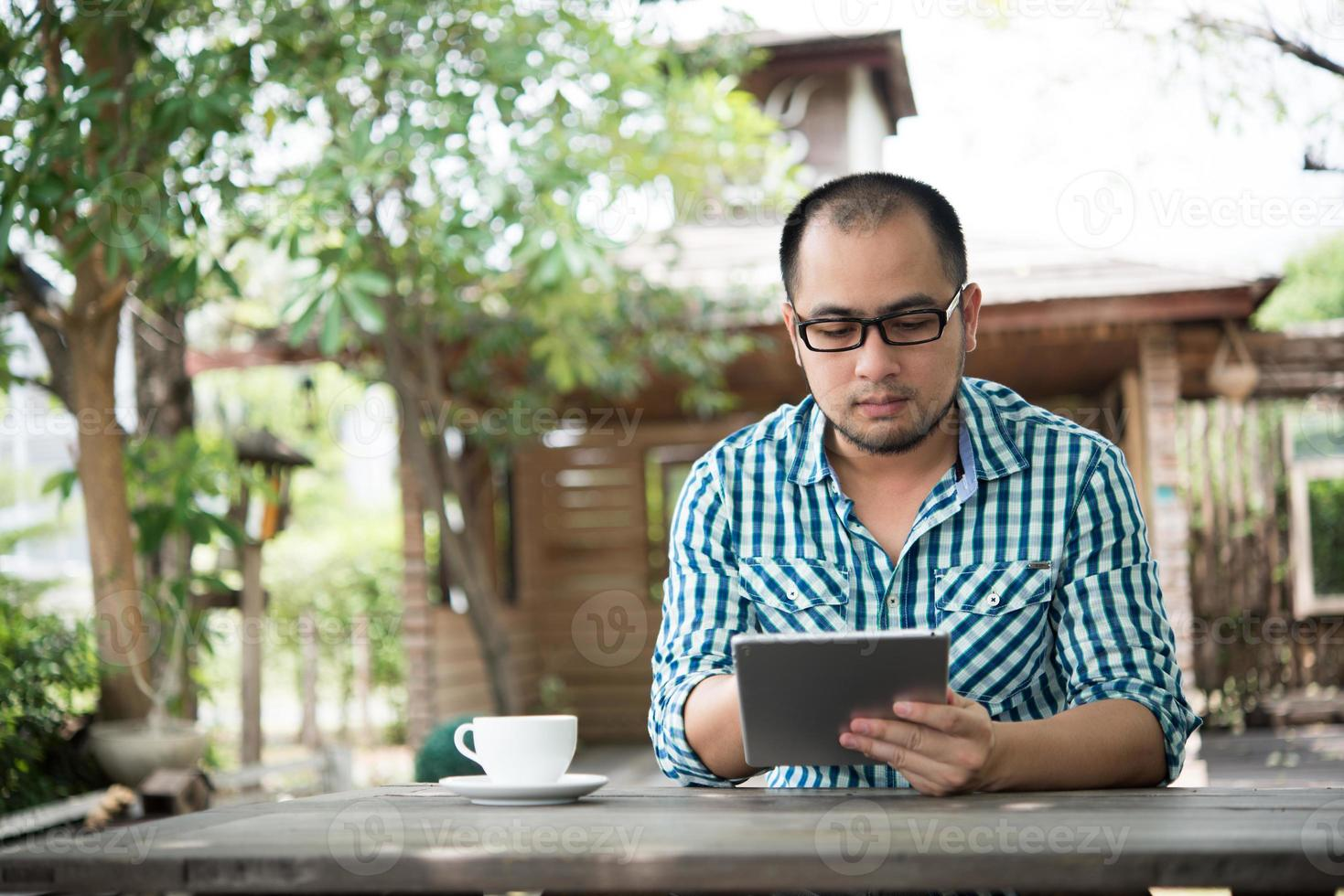 homme d'affaires travaille sur tablette alors qu'il était assis à une table en bois à la maison photo