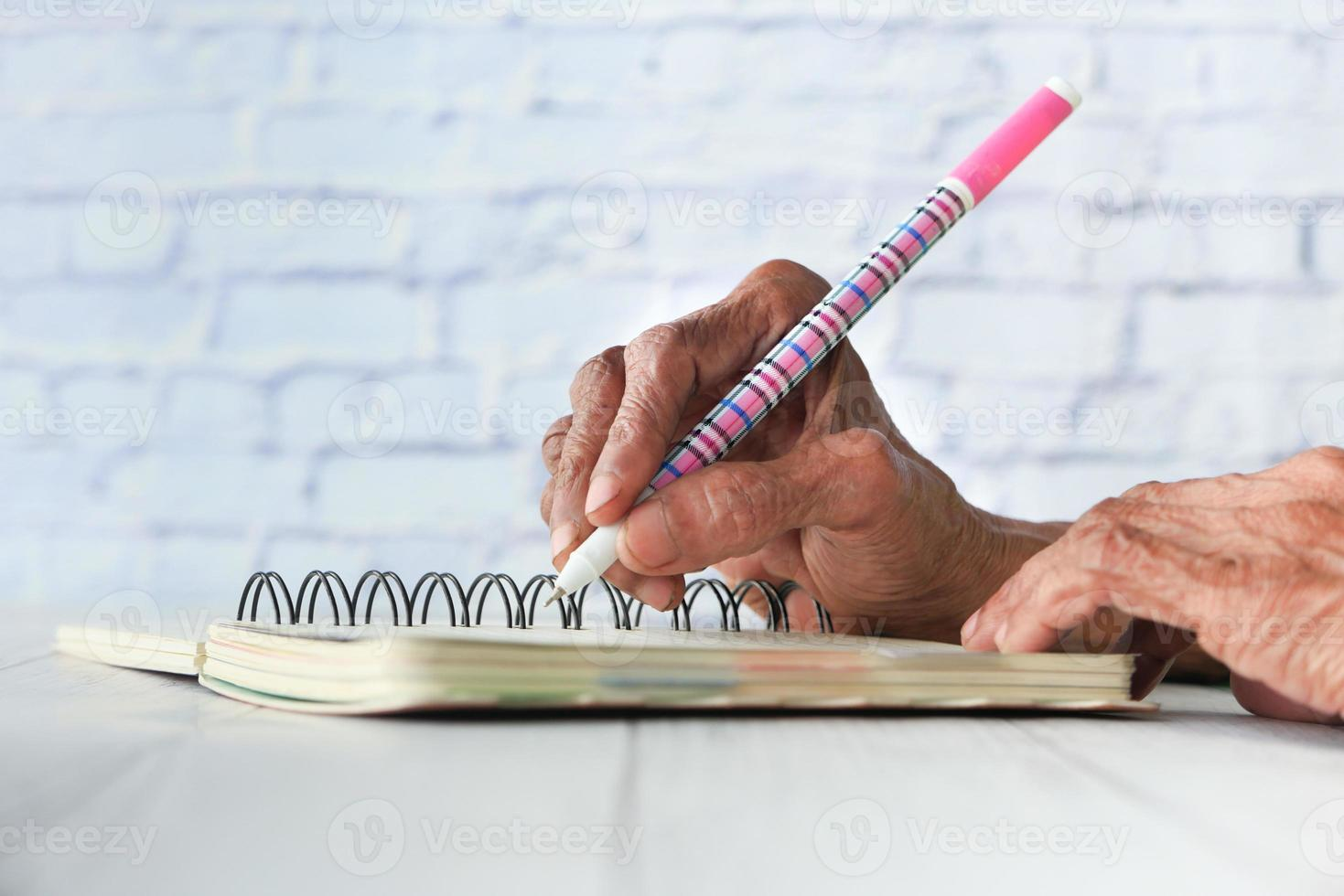 Gros plan des femmes âgées écrivant dans un bloc-notes photo