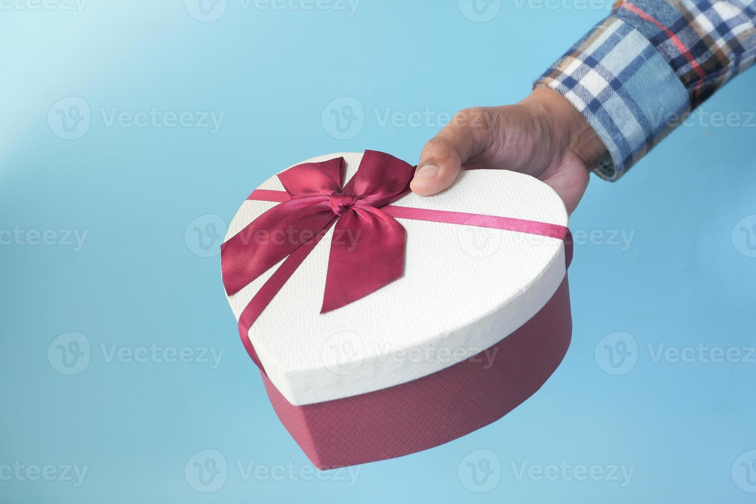 main de l'homme tenant une boîte cadeau en forme de coeur photo