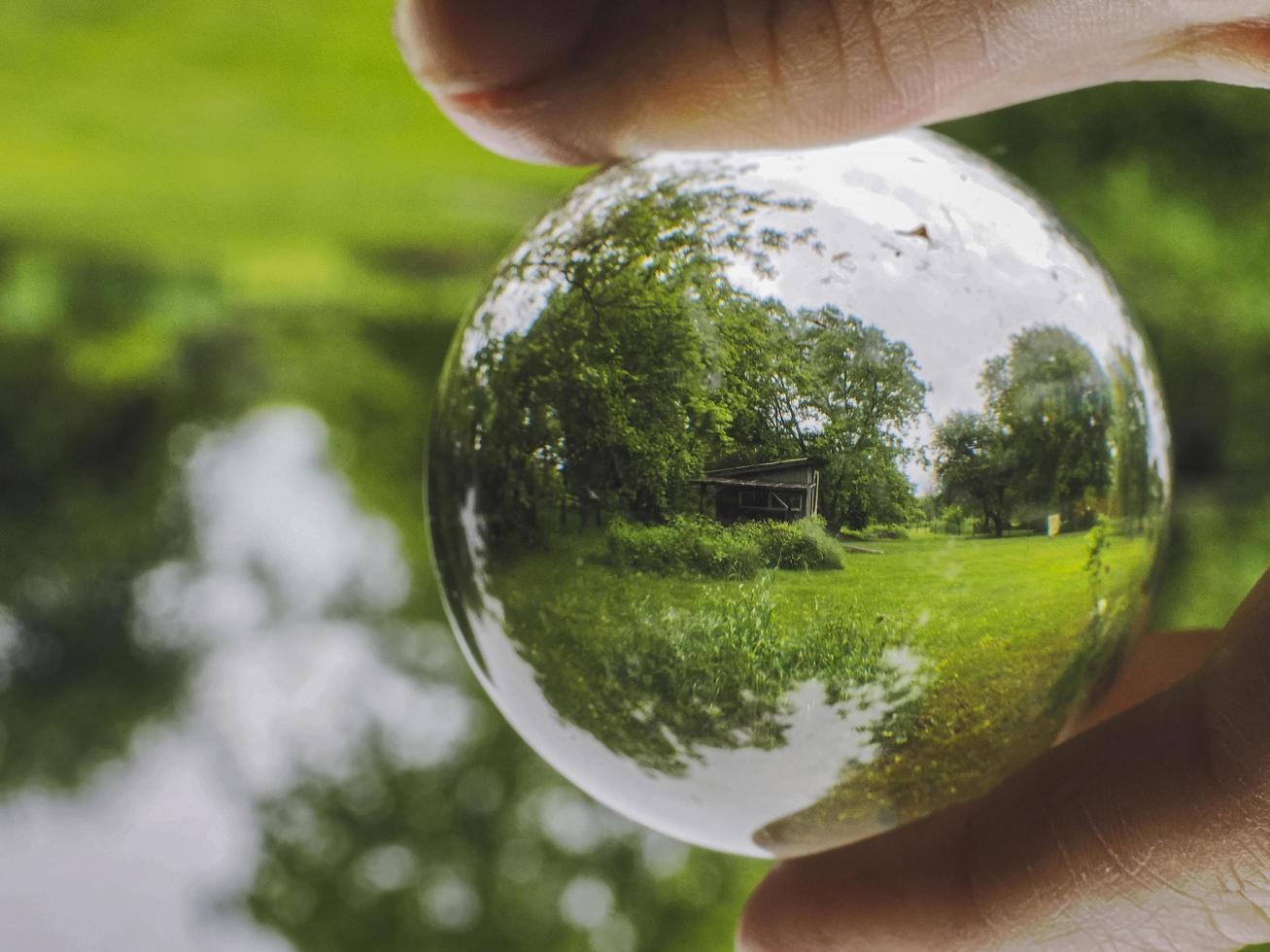 un hangar vu à travers une boule de verre tenue à la main photo