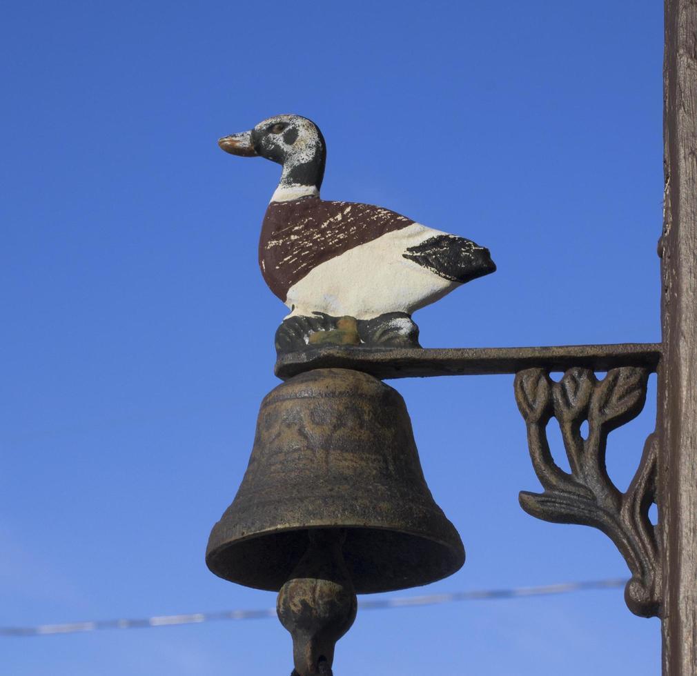 Statue en métal d'un canard et d'une cloche et d'un ciel bleu clair photo