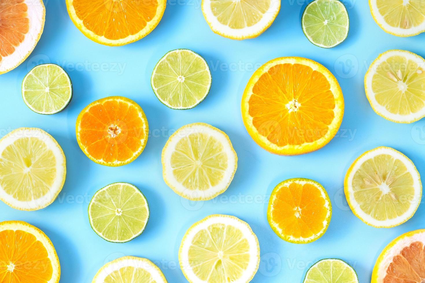 collection de citron vert frais, citron, orange, agrumes, tranche de pamplemousse sur fond bleu. photo