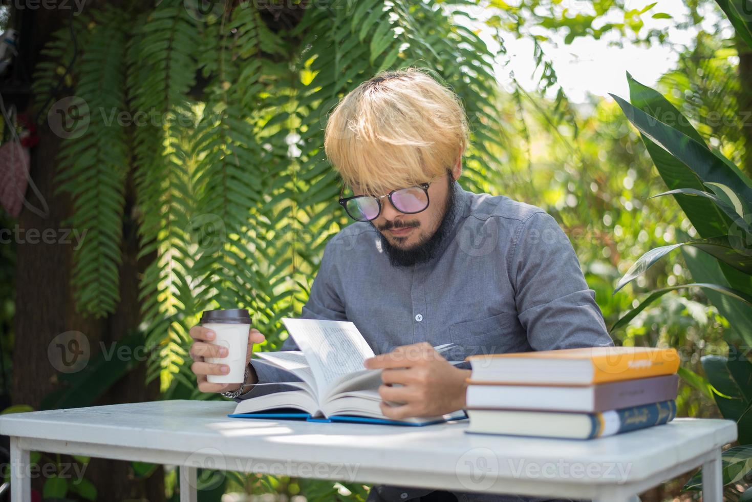 Jeune homme barbe hipster buvant du café en lisant des livres dans le jardin avec la nature photo