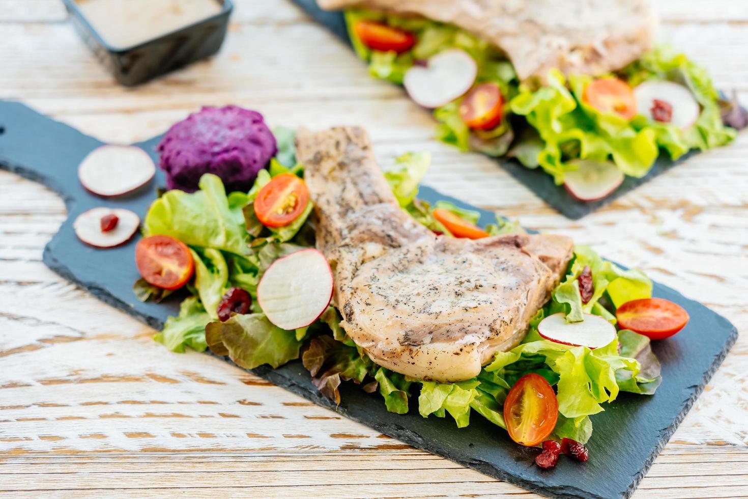 Steak de viande de côtelette de porc barbecue grillé sur plaque noire avec des légumes photo