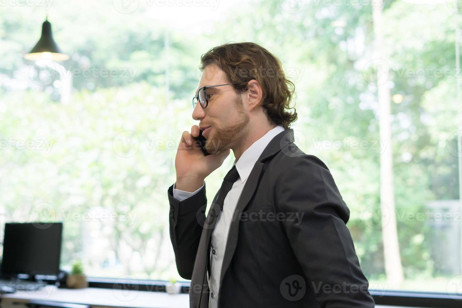 jeune homme d'affaires à l'aide de smartphone tout en se tenant au bureau photo