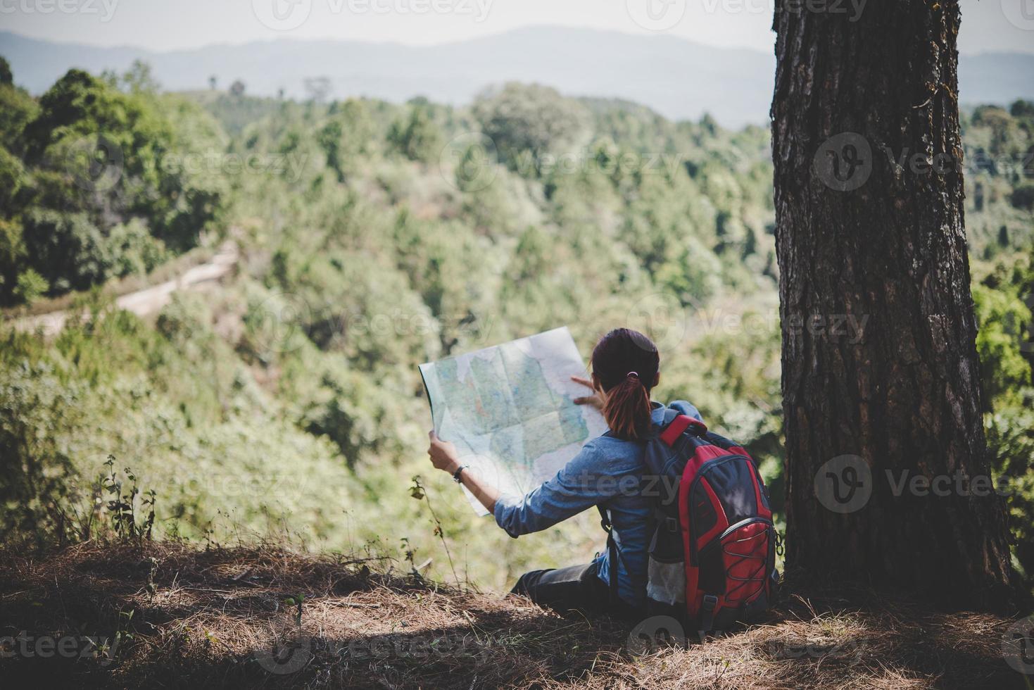 Randonneur jeune femme lisant une carte lors d'une randonnée photo