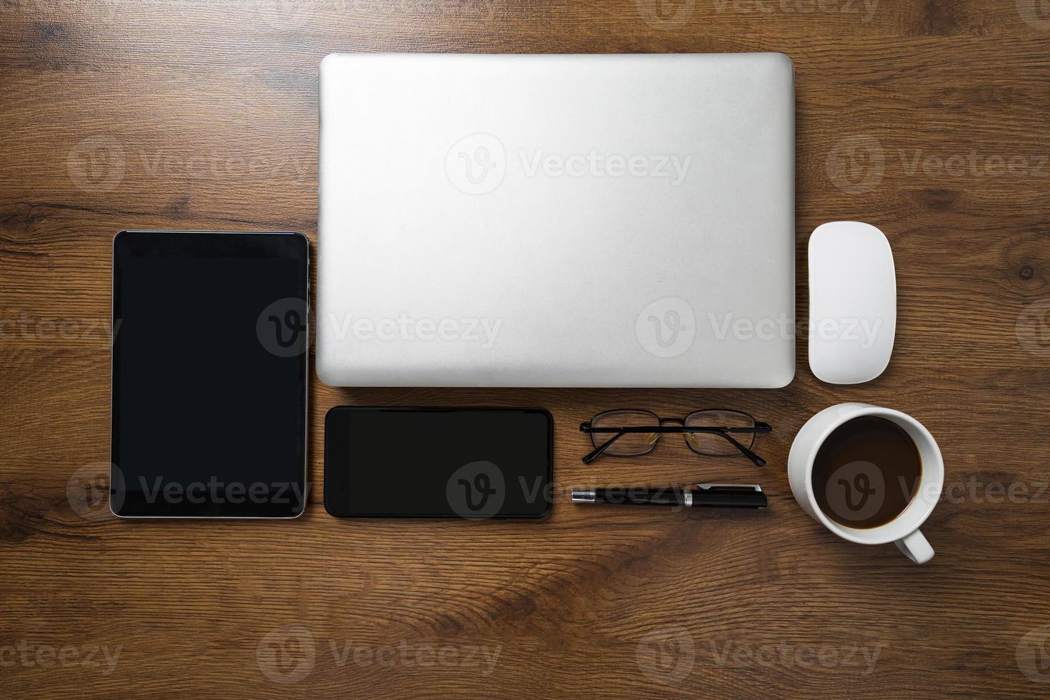 Vue de dessus de l'espace de travail avec ordinateur portable, smartphone, tablette, tasse à café, lunettes et stylo sur table en bois photo