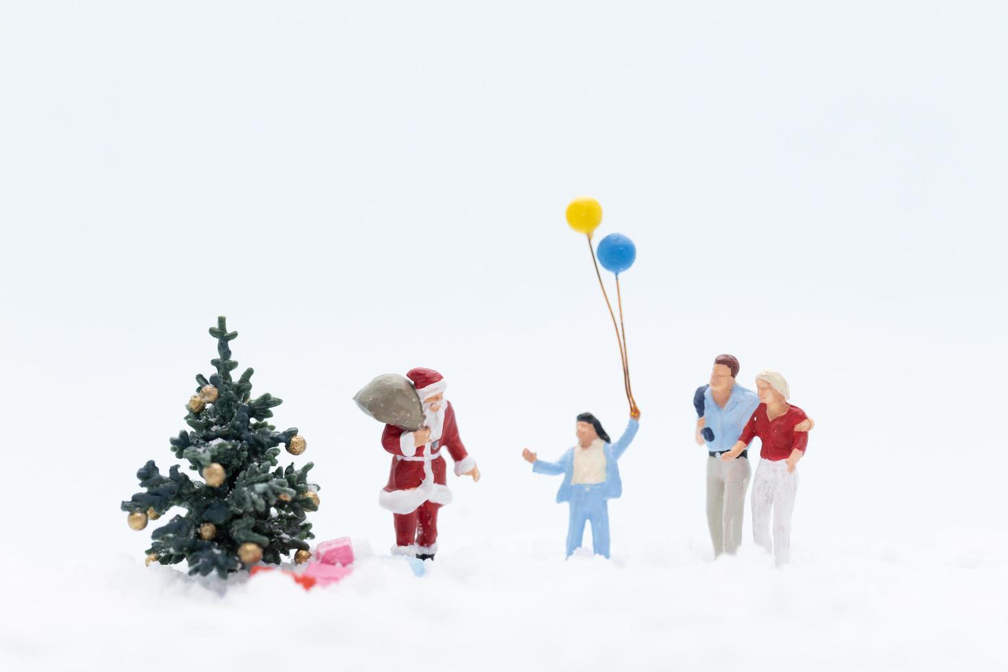 personnes miniatures avec le père noël avec des cadeaux pour les enfants, concept de noël photo