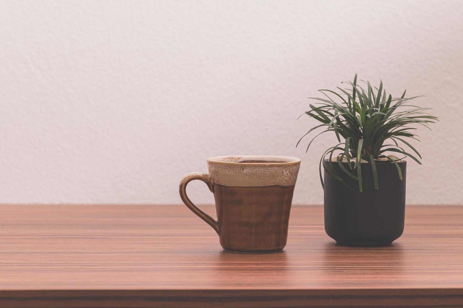 tasse à café et plante en pot sur la table photo