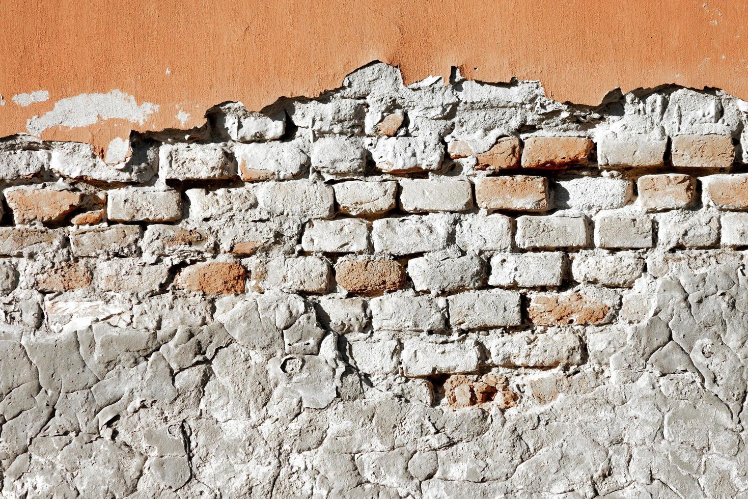 Vieux mur de briques partiellement endommagé photo