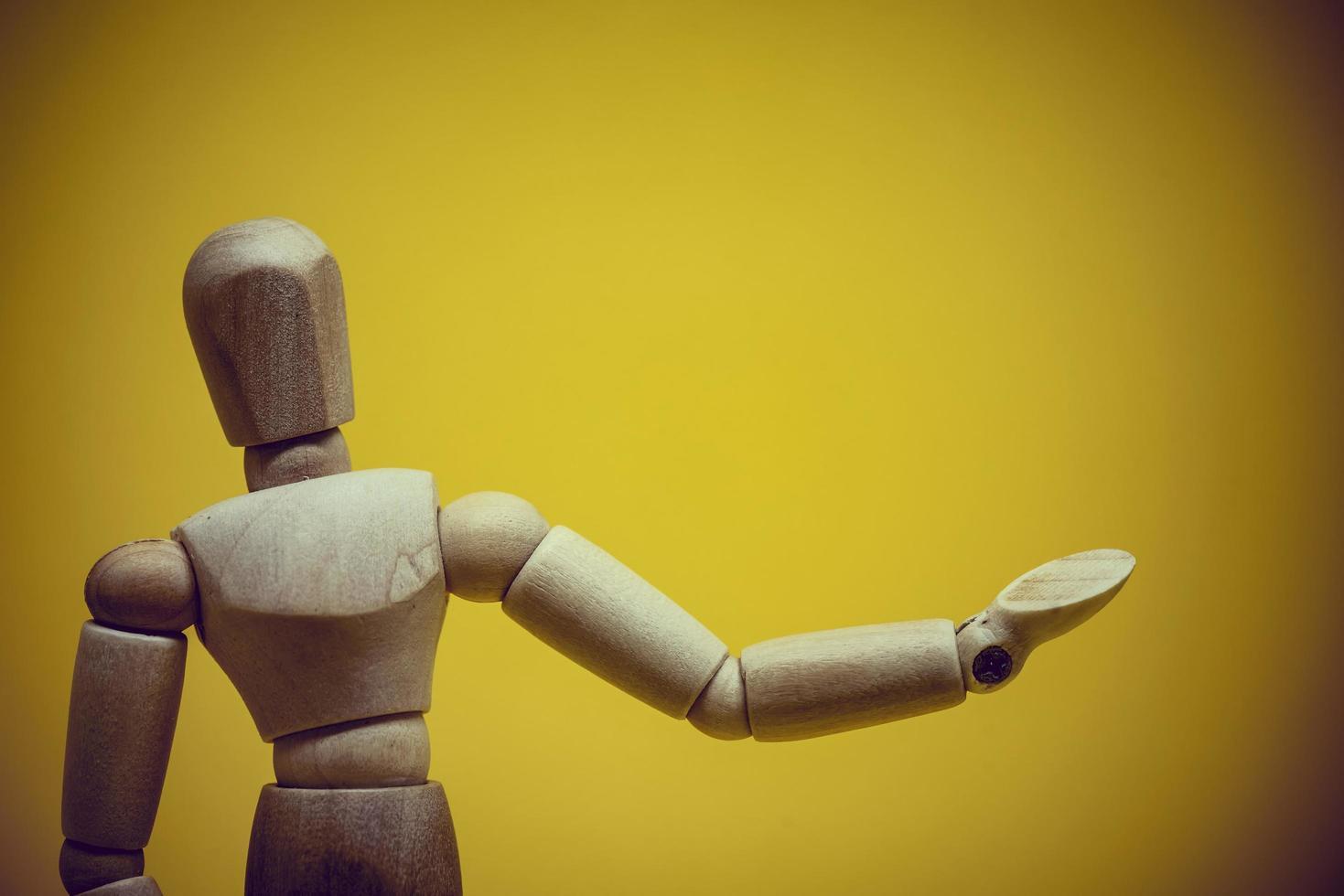 mannequin en bois présentant un objet invisible photo