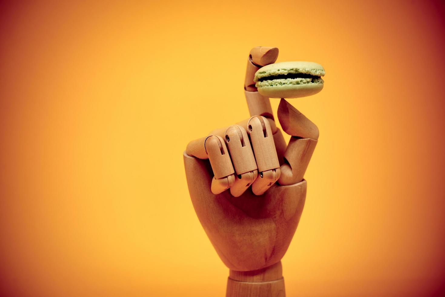 main en bois tenant le macaron photo