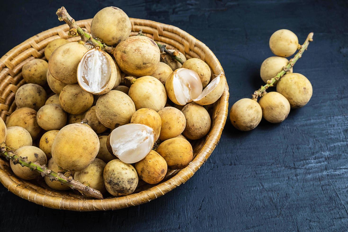 Longkong ou langsat fruits dans un panier en osier sur un fond de bois noir photo