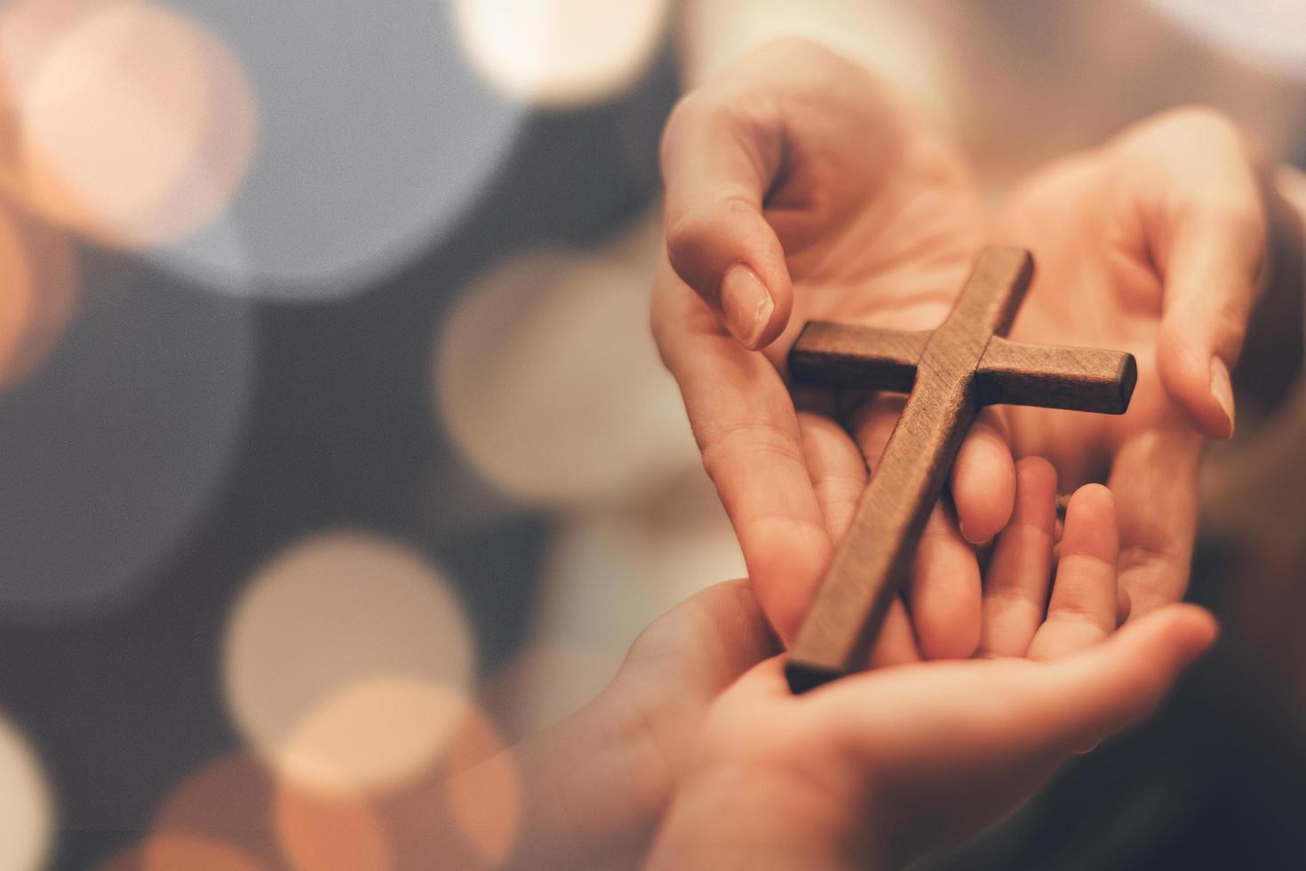 personne remettant une croix en bois photo