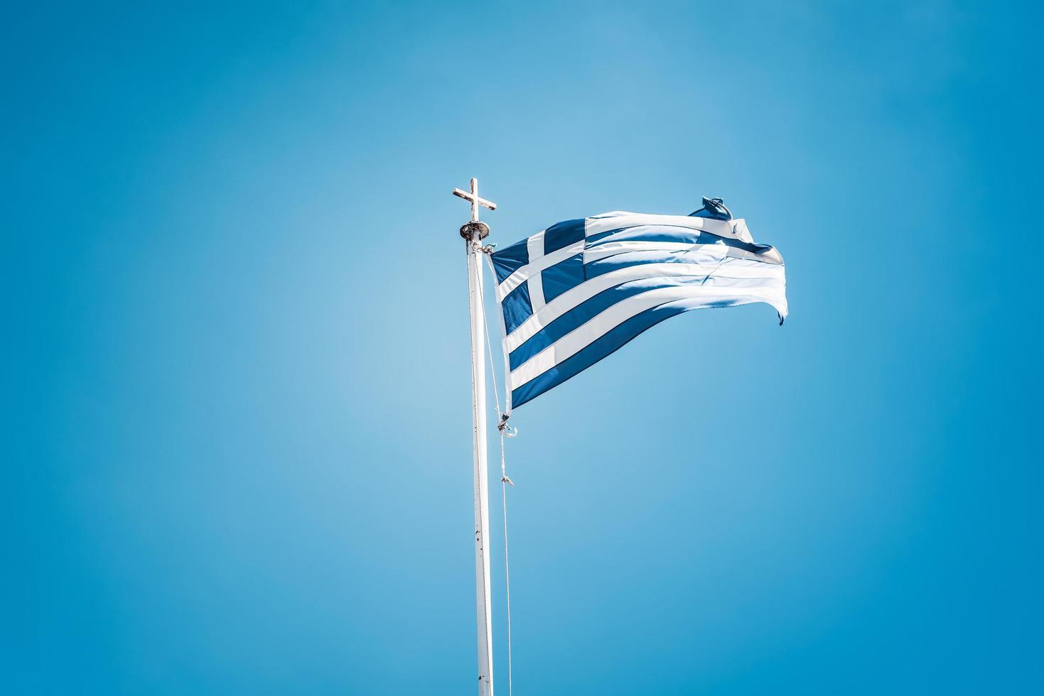 Drapeau grec contre le ciel bleu photo
