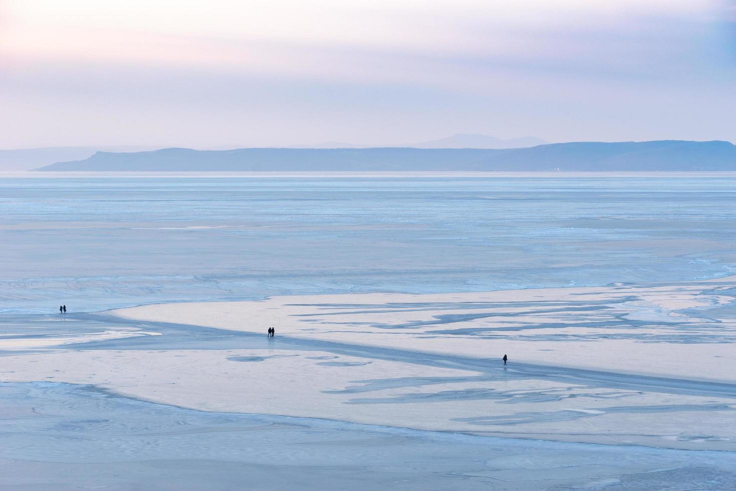 les gens marchent le long de la surface glacée avec des montagnes et un ciel nuageux en arrière-plan photo