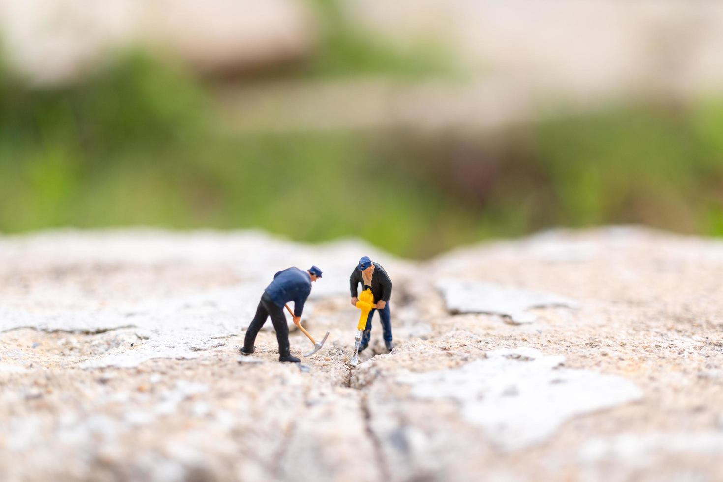 travailleurs miniatures travaillant sur du béton avec des fissures, concept de travail d'équipe photo