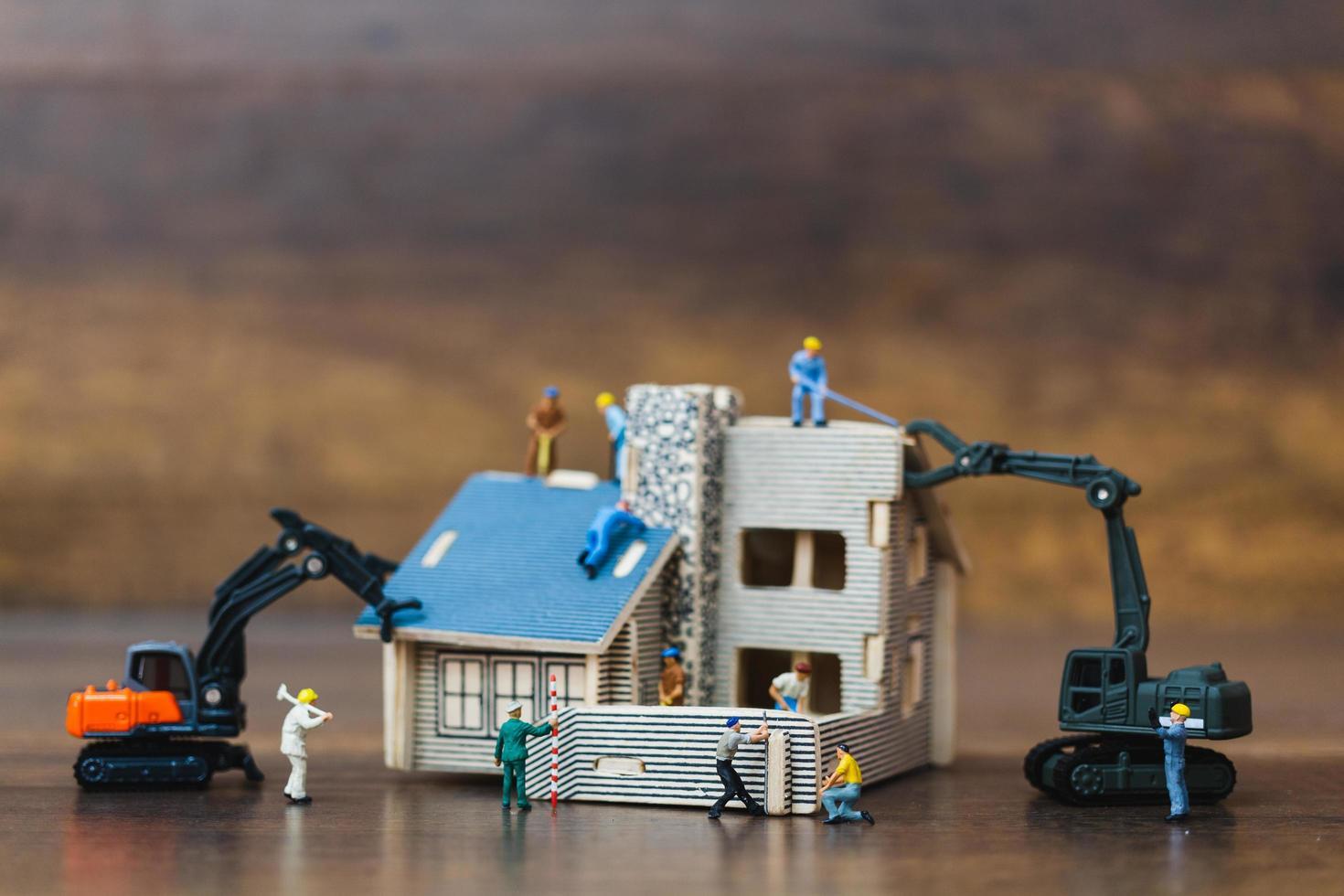 travailleurs miniatures construisant une maison, concept de rénovation domiciliaire photo