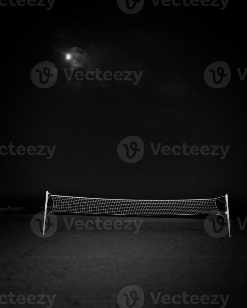 Terrain de volley-ball solitaire sur une plage par une nuit de pleine lune photo