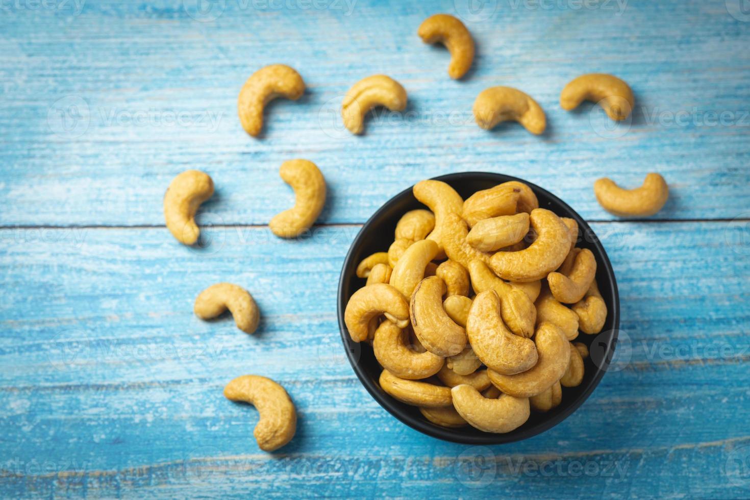 Bol de noix de cajou décortiquées sur une table bleue photo
