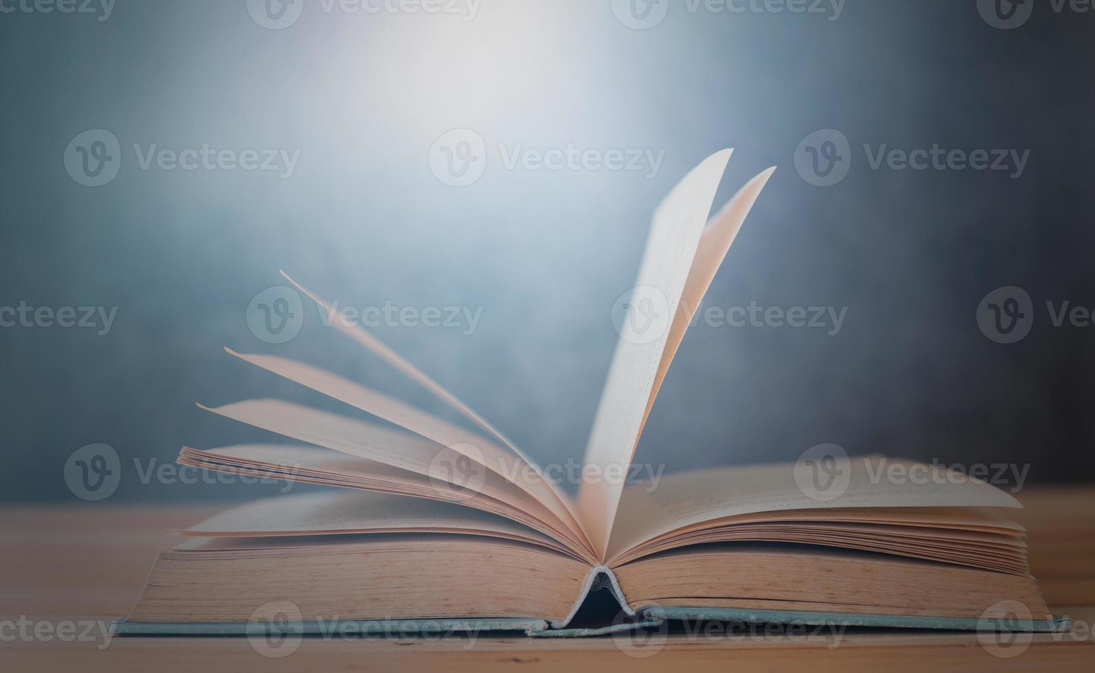 livre ouvert sur table en bois avec fond bleu photo