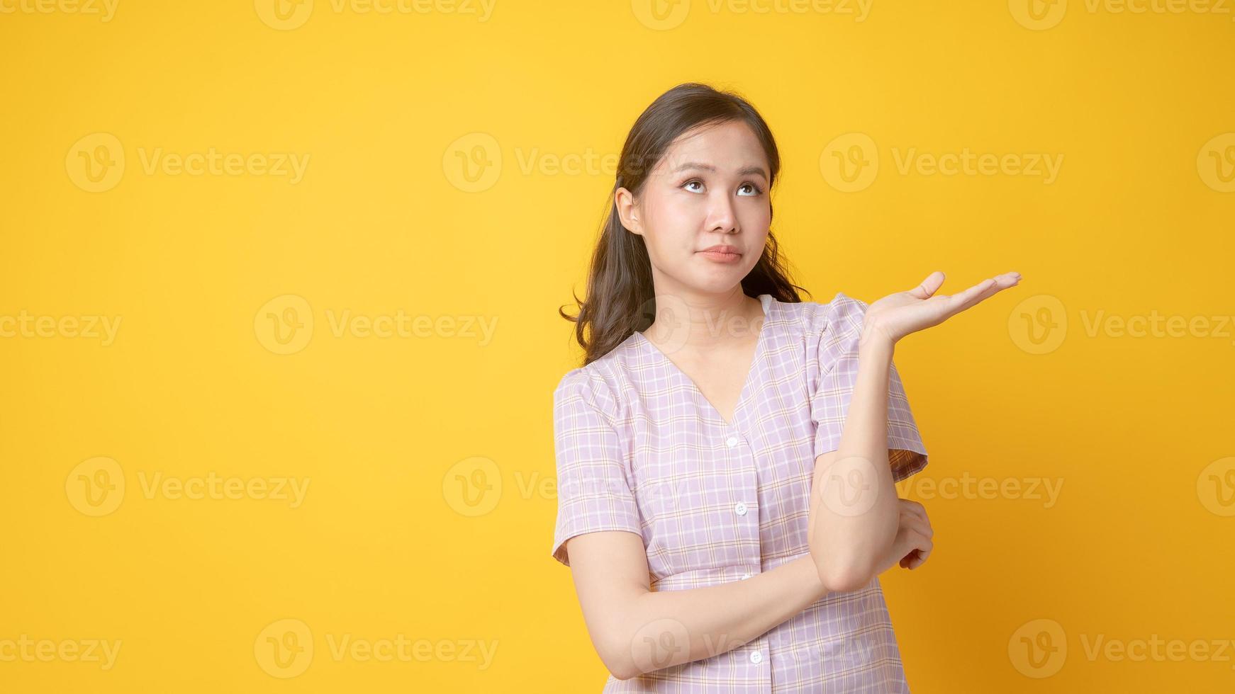 Femme asiatique avec les bras croisés et une paume vers le haut sur fond jaune photo