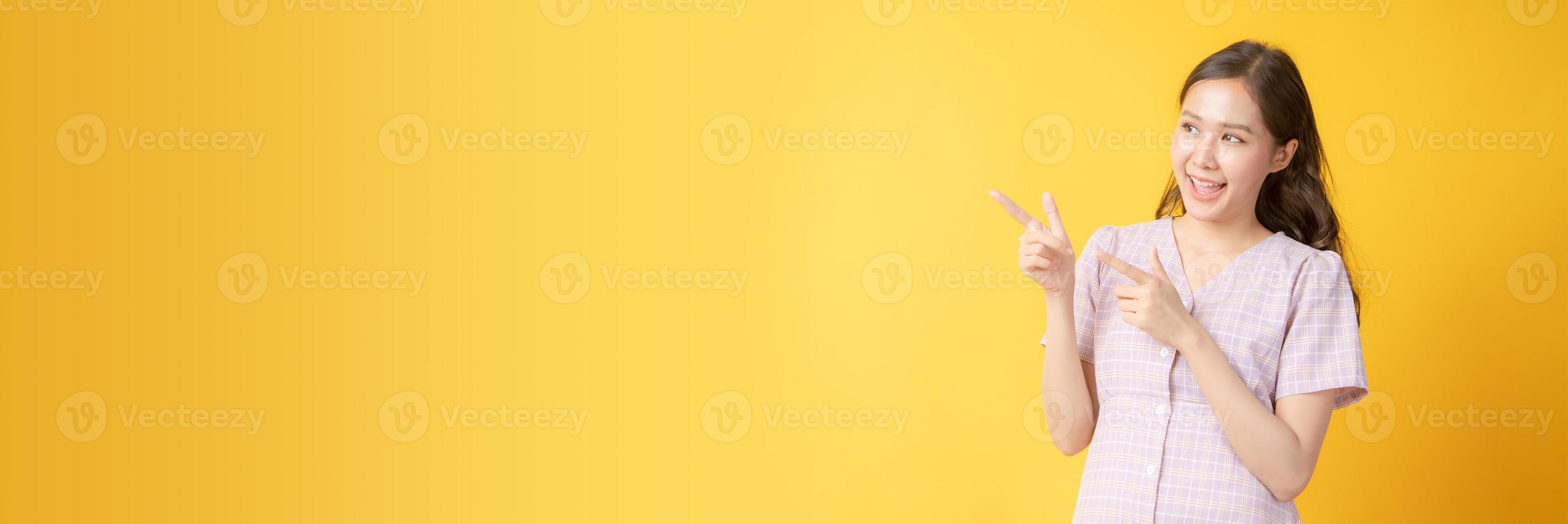 Femme asiatique souriant et faisant des gestes vers l'espace de copie sur fond jaune photo