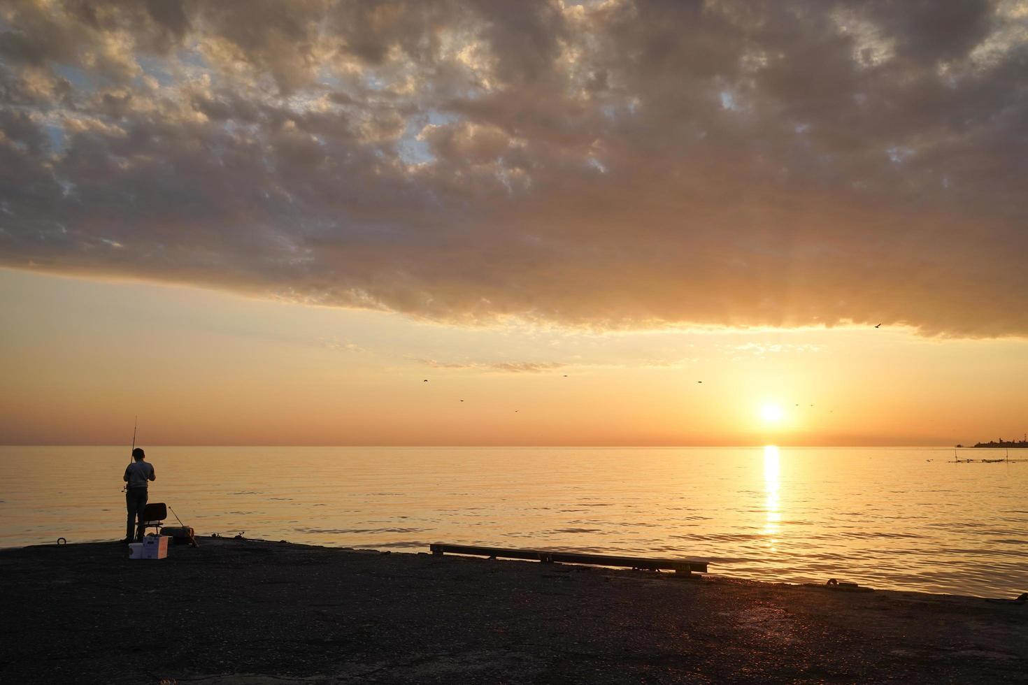 Silhouette d'un homme pêchant sur une jetée avec un coucher de soleil nuageux coloré photo