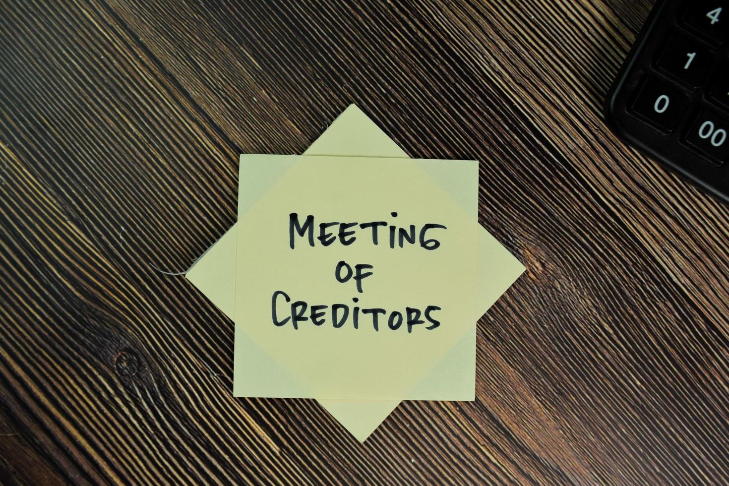 Réunion des créanciers écrit sur pense-bête isolé sur table en bois photo
