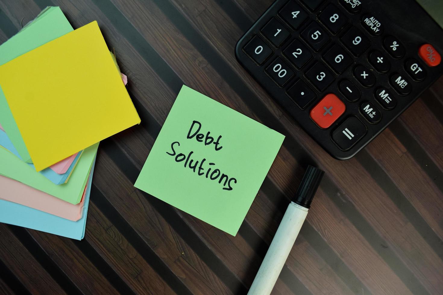 Solution de la dette écrite sur pense-bête isolé sur table en bois photo