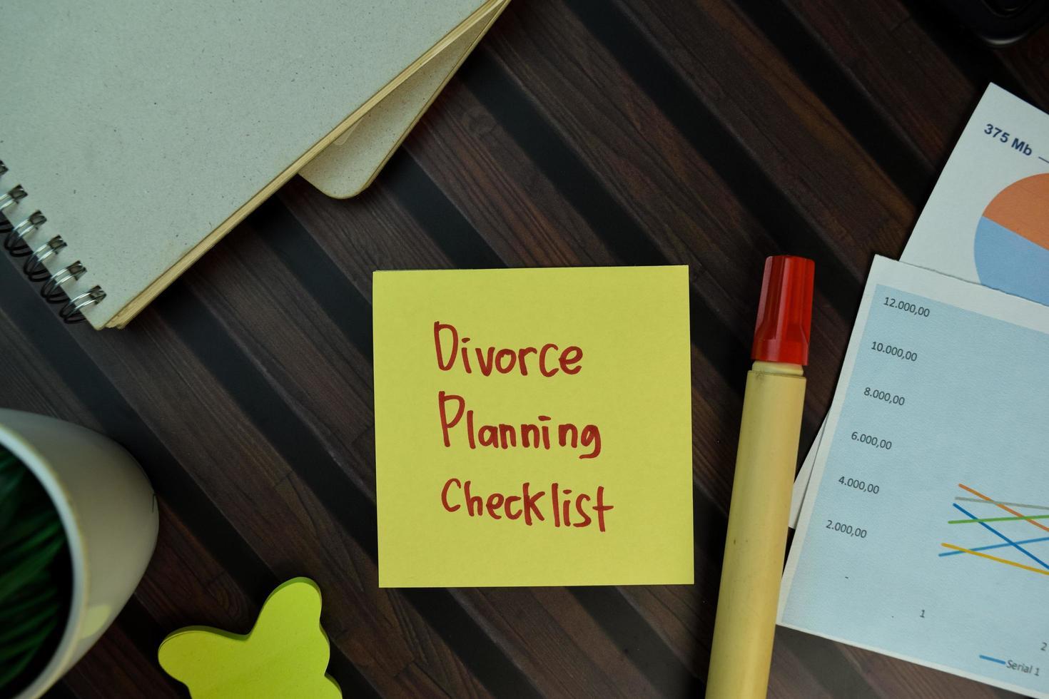 Liste de contrôle de la planification du divorce écrite sur pense-bête isolé sur table en bois photo