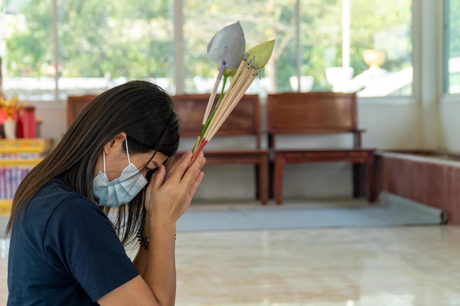Jeune femme asiatique faisant un vœu dans un temple, concept de vie, espoir, croyance et bonne chance photo