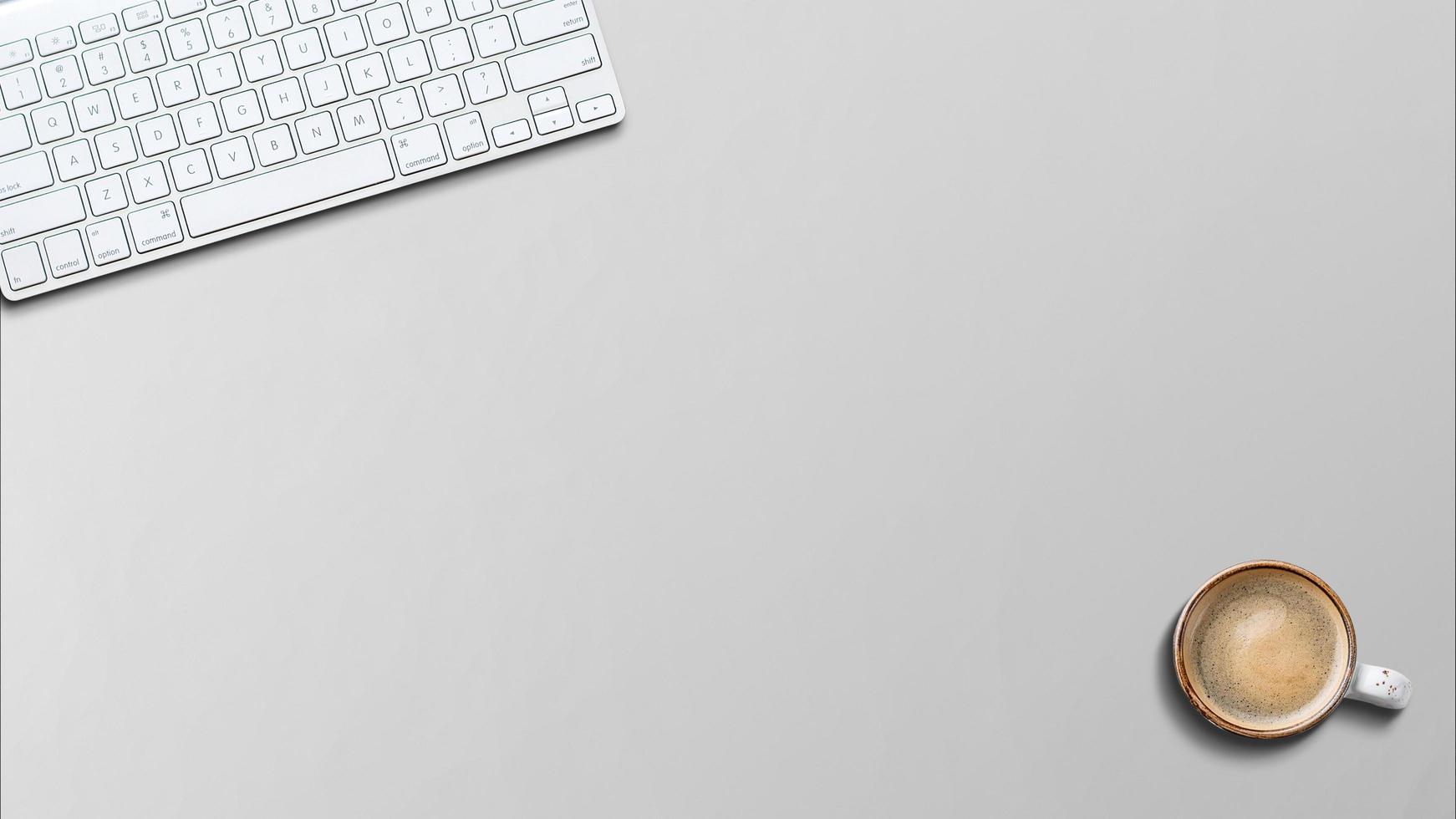 Clavier en aluminium moderne sur la table en bois au bureau avec du café sur la table photo