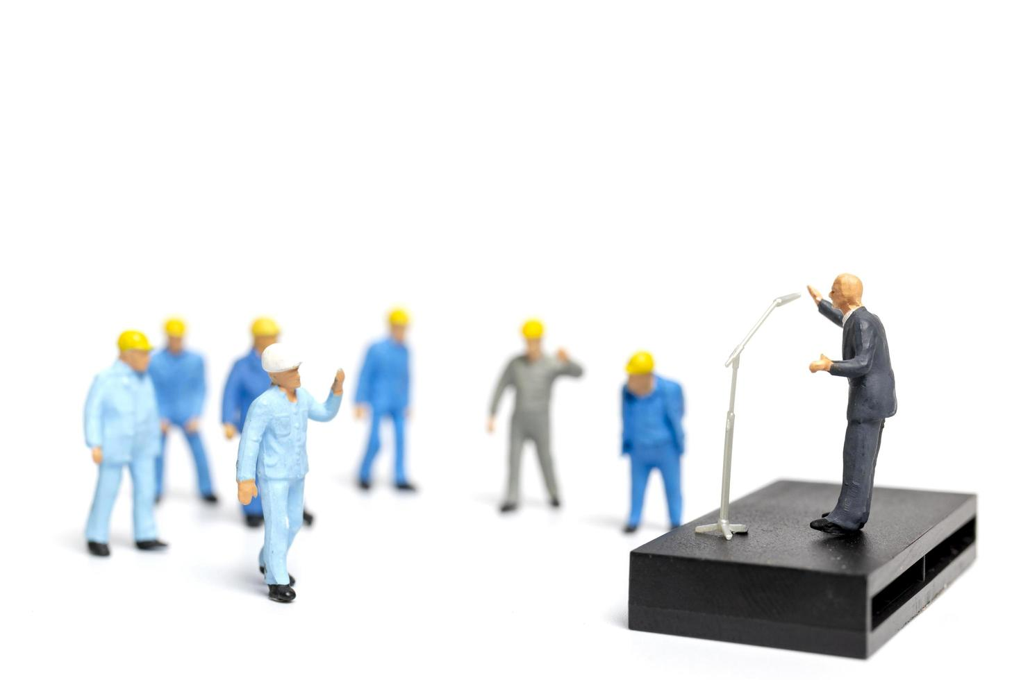 Personnes miniatures écoutant un politicien s'exprimant lors d'un rassemblement électoral photo