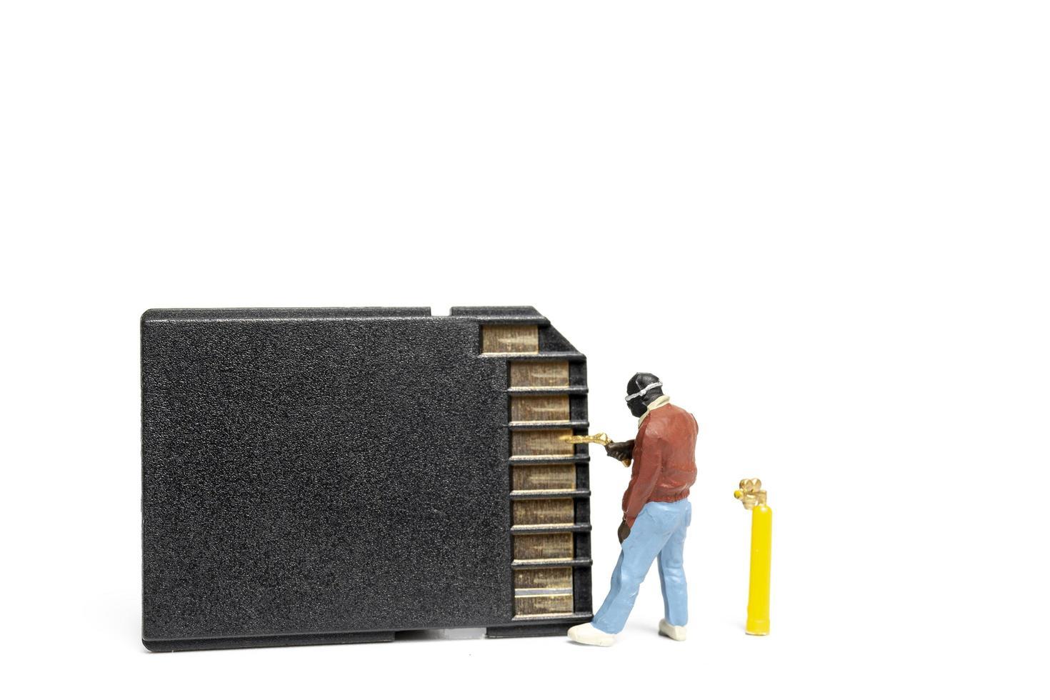 Technicien miniature fixation de cartes sd pile sur fond blanc photo