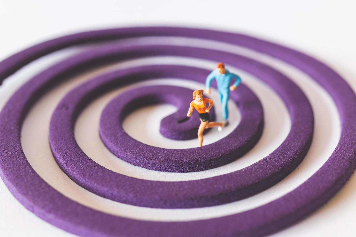 Couple miniature fonctionnant sur un champ circulaire violet photo