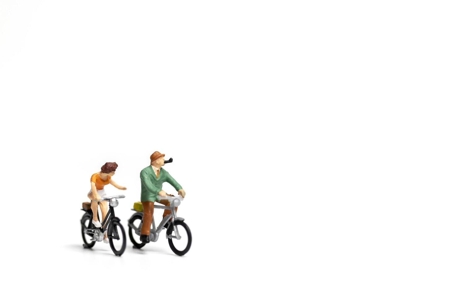Couple miniature à bicyclette sur fond blanc, concept de la Saint-Valentin photo