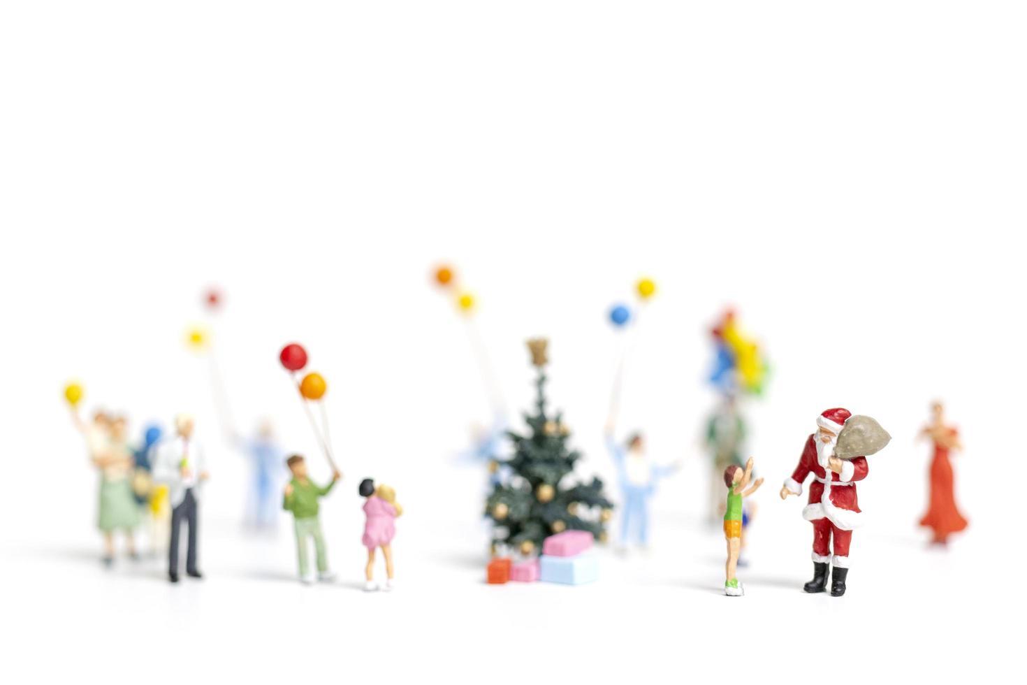 Père Noël miniature tenant des cadeaux pour une famille heureuse, Noël et bonne année concept photo