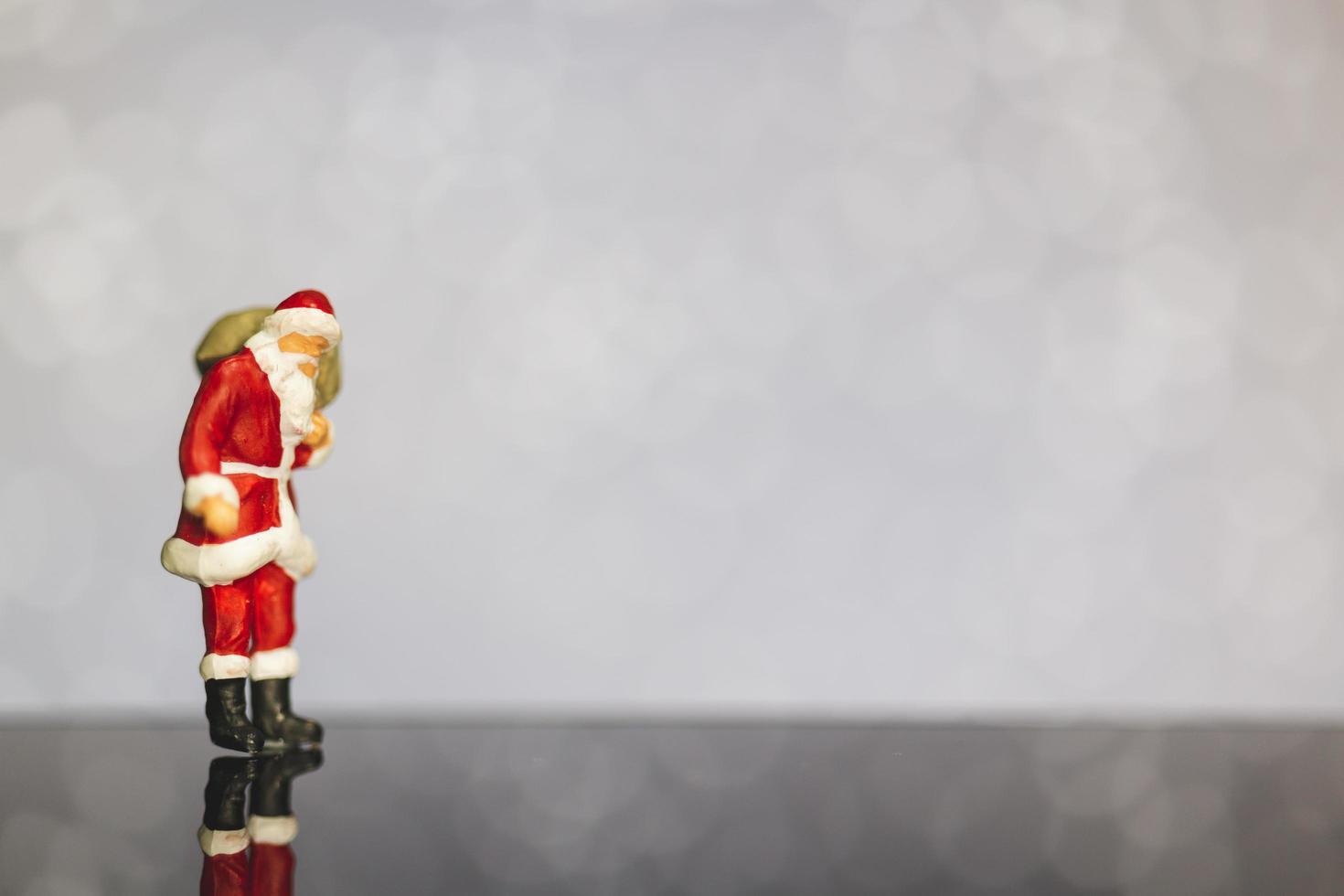 Père Noël miniature portant un sac sur un fond de bokeh, joyeux Noël et bonne année concept. photo