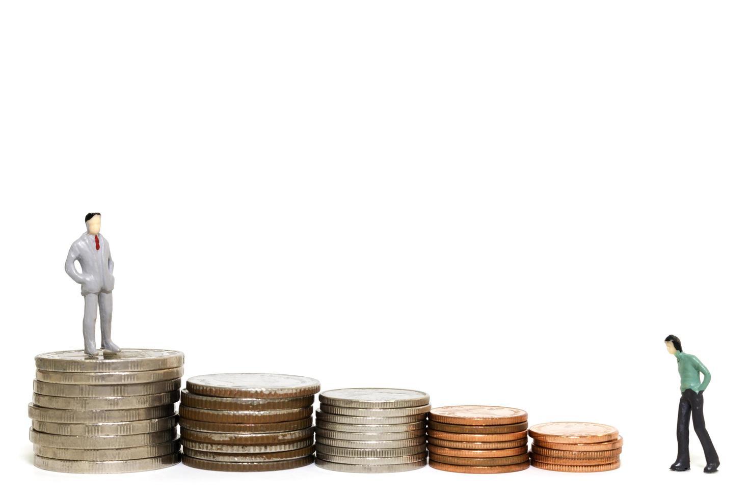 Hommes d'affaires miniatures avec une pile de pièces sur fond blanc photo