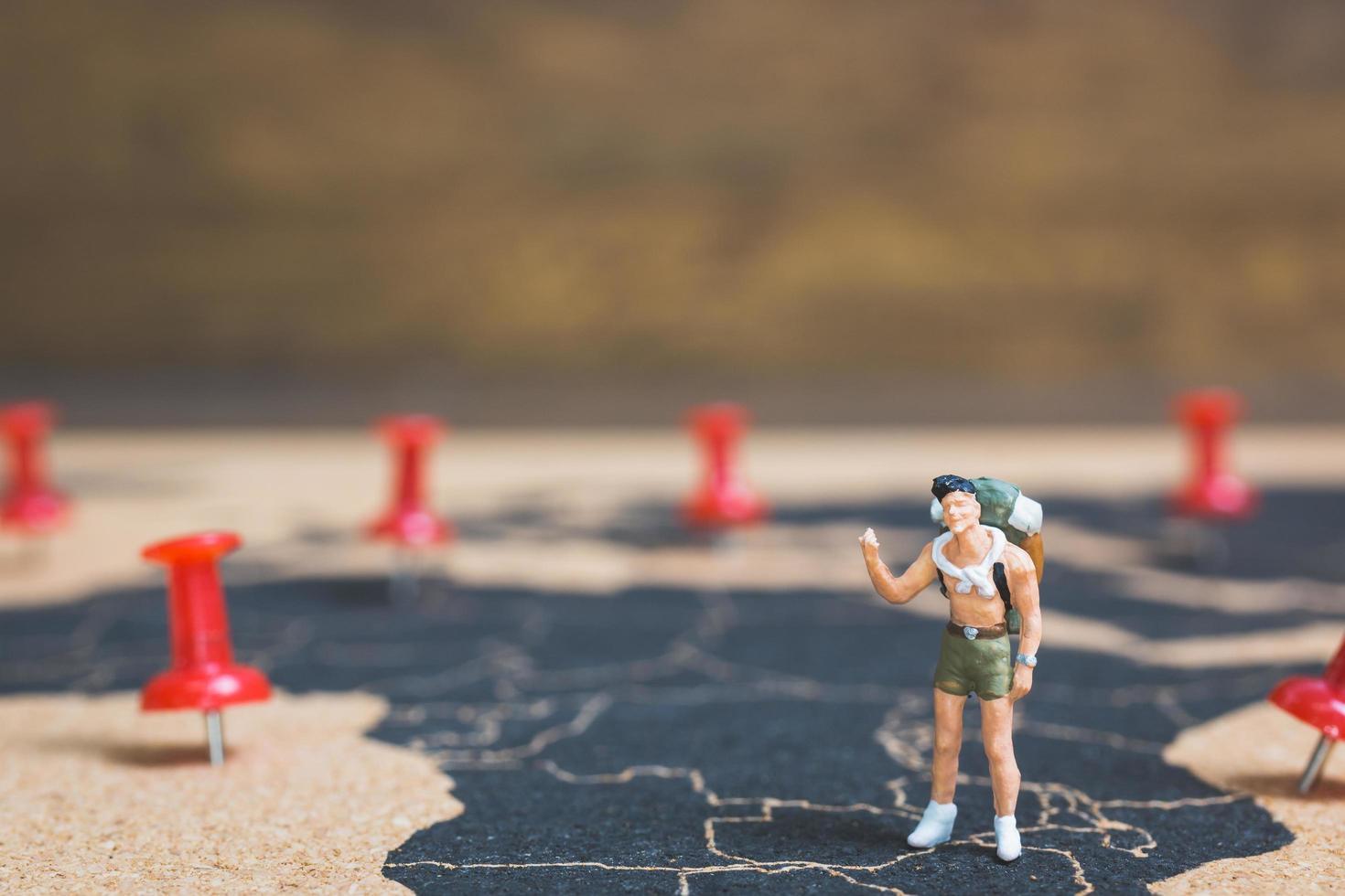 Routard miniature marchant sur une carte du monde, concept de tourisme et de voyage photo