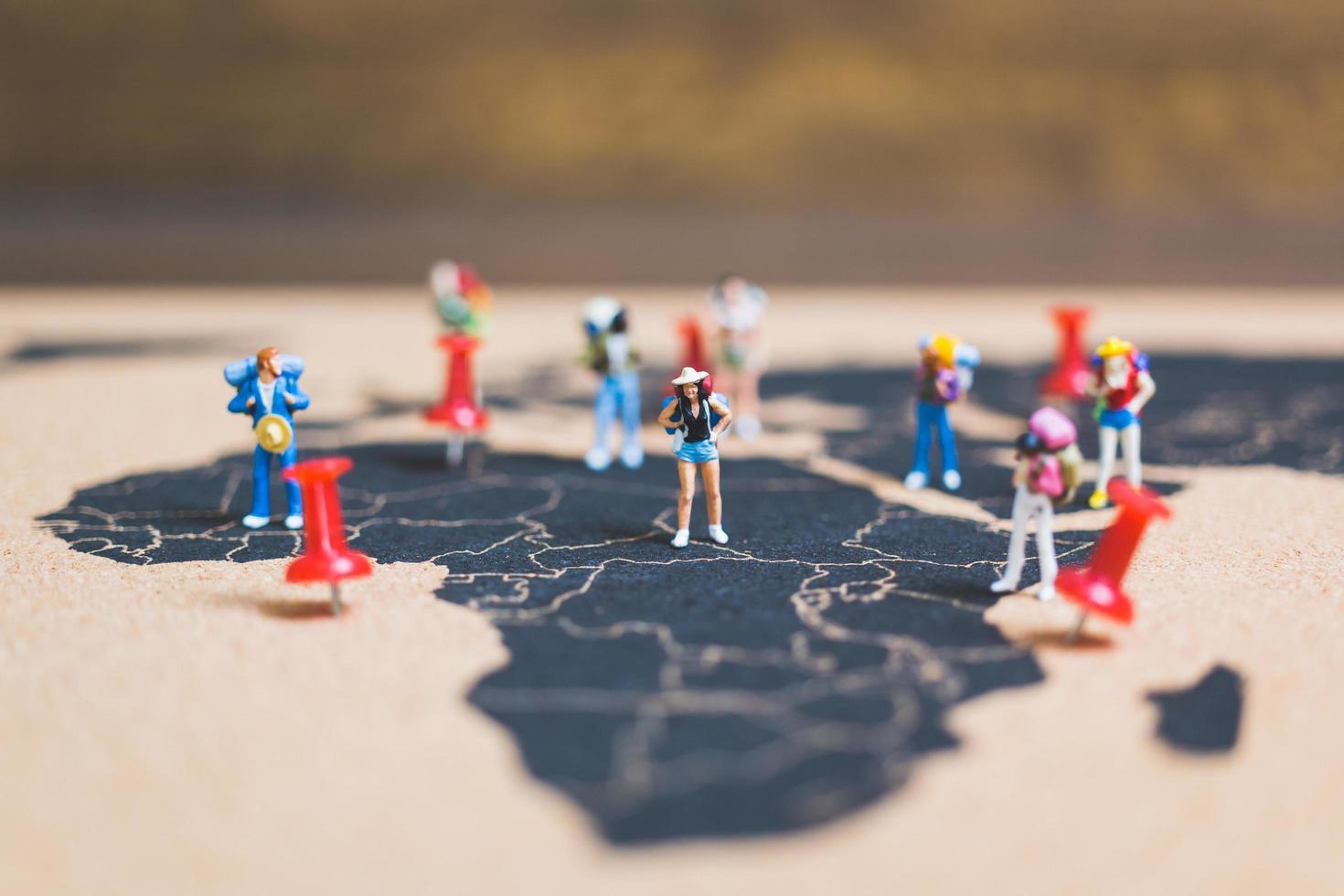 routards miniatures marchant sur une carte du monde, concept de tourisme et de voyage photo
