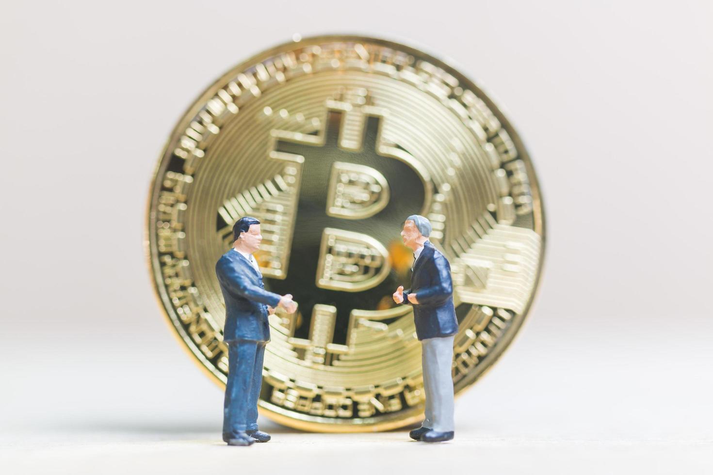 Hommes d'affaires miniatures debout devant une pièce de monnaie crypto-monnaie bitcoin, concept d'entreprise photo