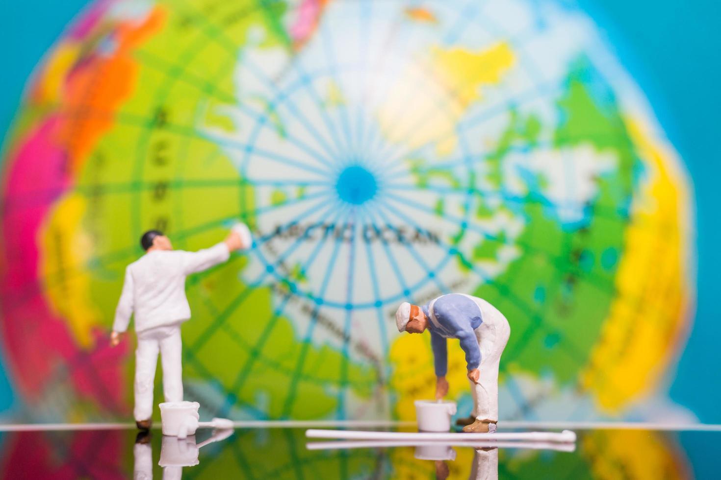 Peintres miniatures peinture sur un globe, concept de jour de la terre photo
