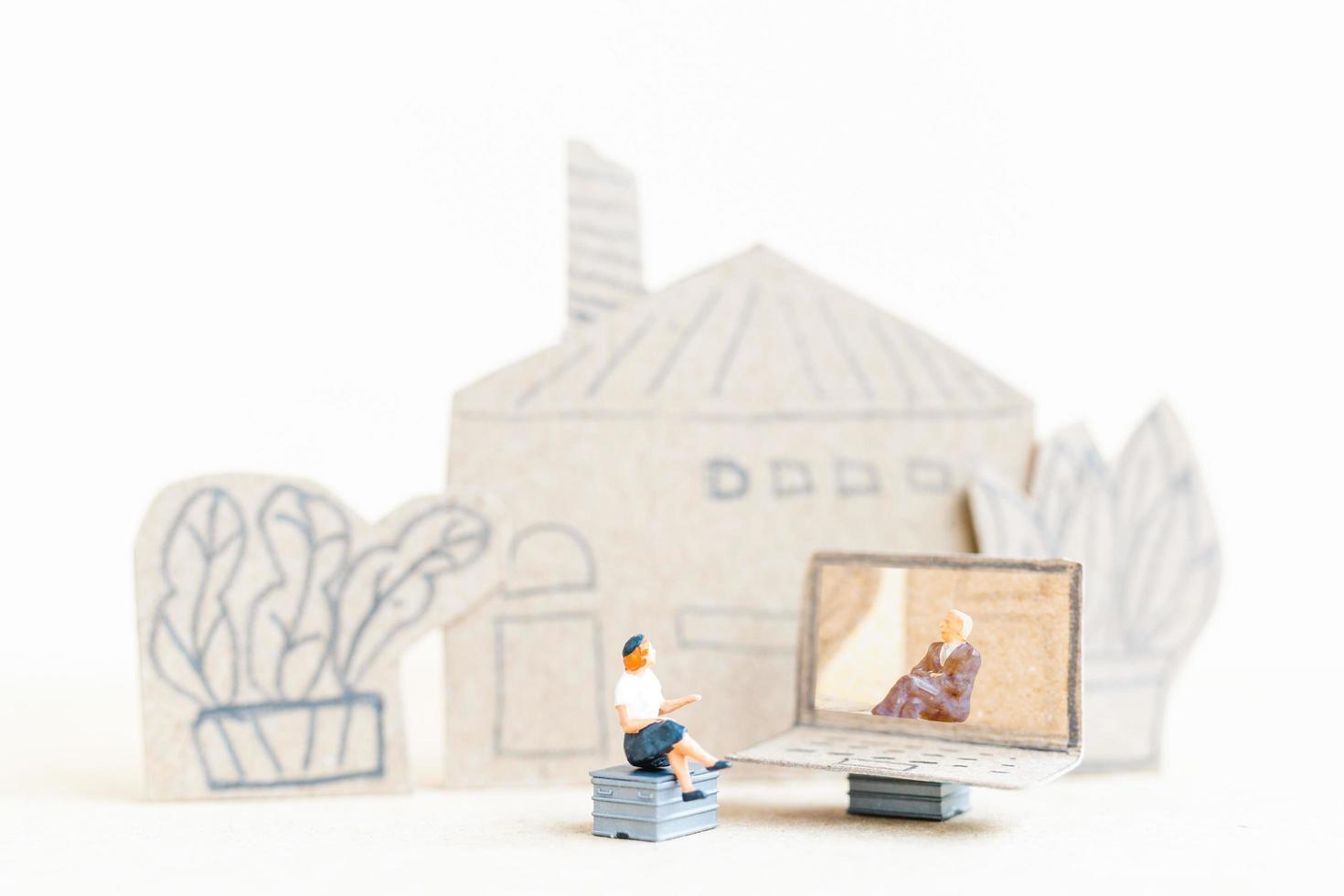 personne miniature travaillant sur un ordinateur portable, travail à la maison concept photo