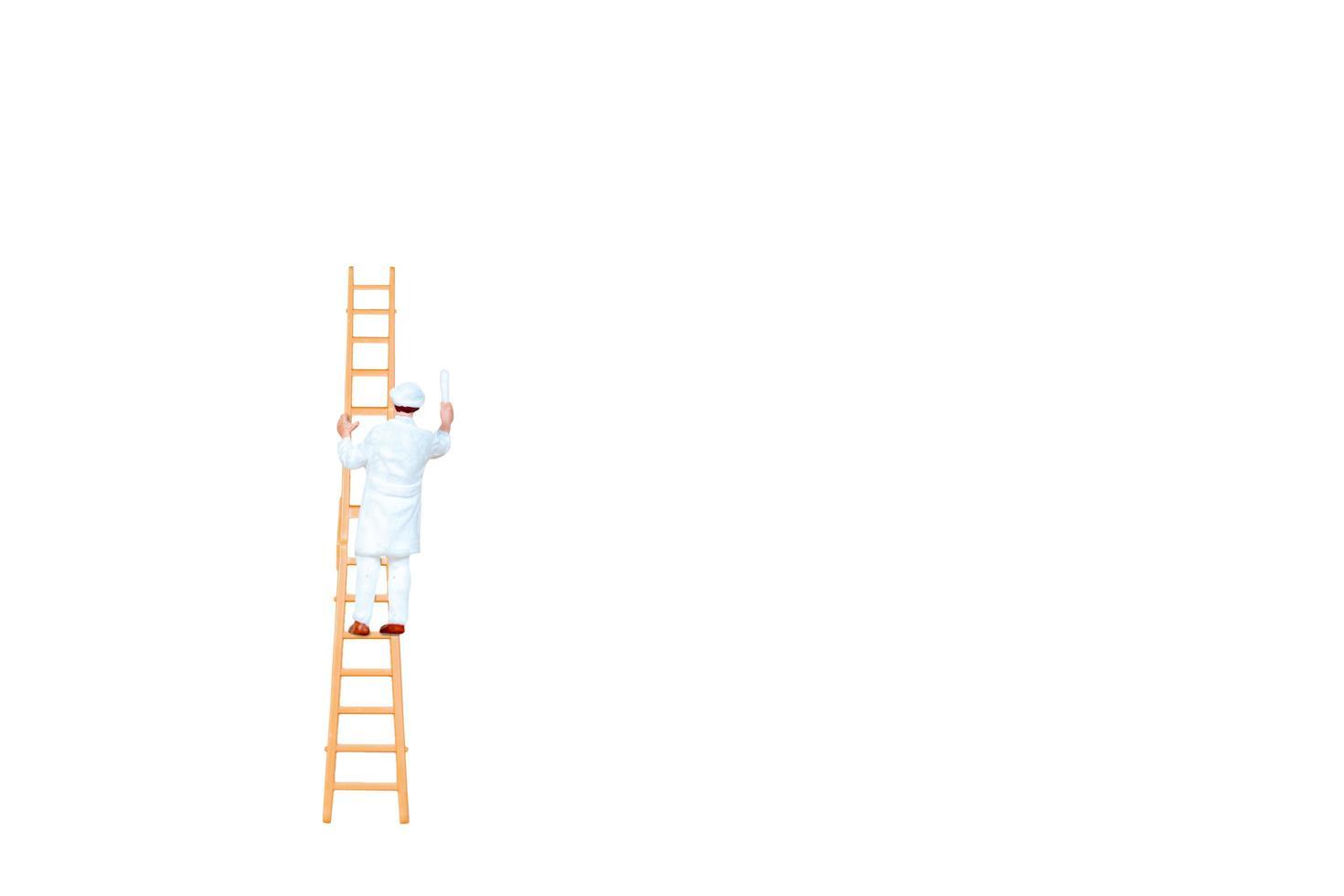 Personne miniature avec une échelle tenant un pinceau devant un fond de mur blanc photo